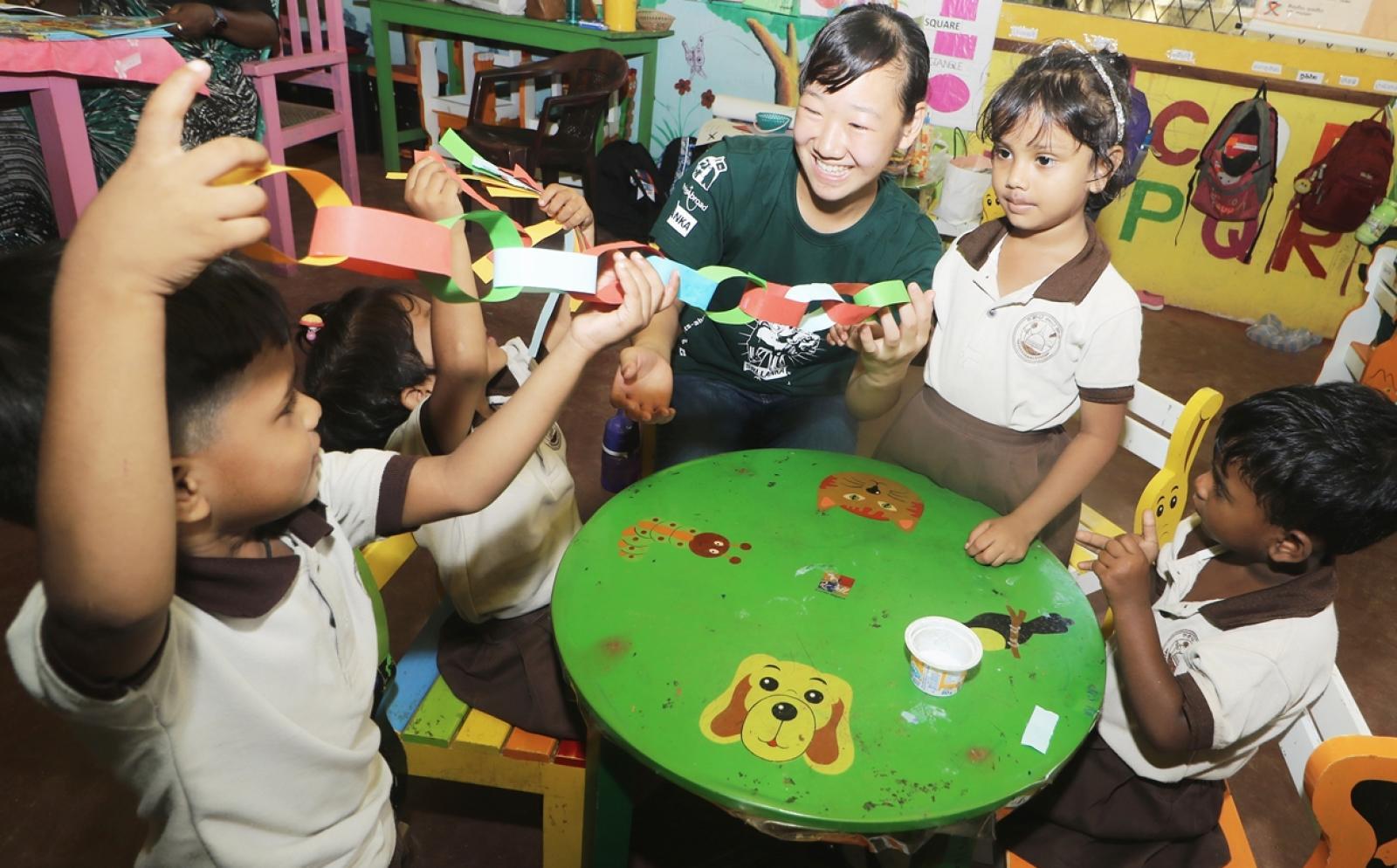 日本出身の高校生ボランティアがスリランカの子供たちと図画工作にあたる